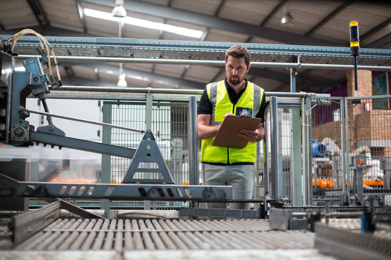fabrika işçisi üretim bandını denetliyor ve elindeki rapora yazıyor