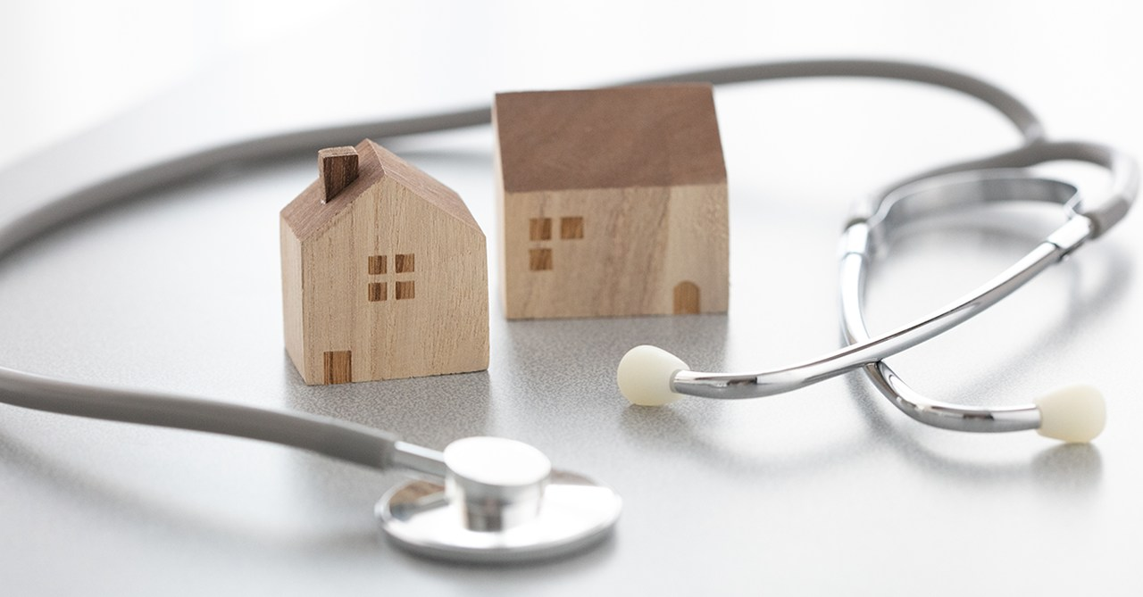 2 küçük kahverengi ev maketinin yanında stetoskop