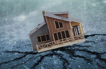 depreme dayanıklı ev temasına uygun küçük kahverengi ev görseli, altında da çatlak bir zemin