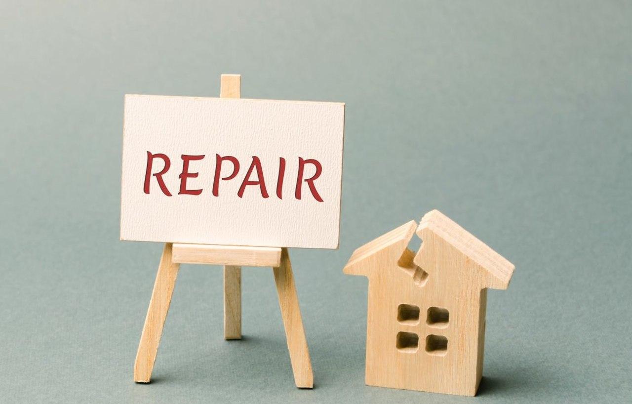 küçük çatlak bir ev maketinin yanında tamir etmek anlamına gelen ingilizce repair tabelası