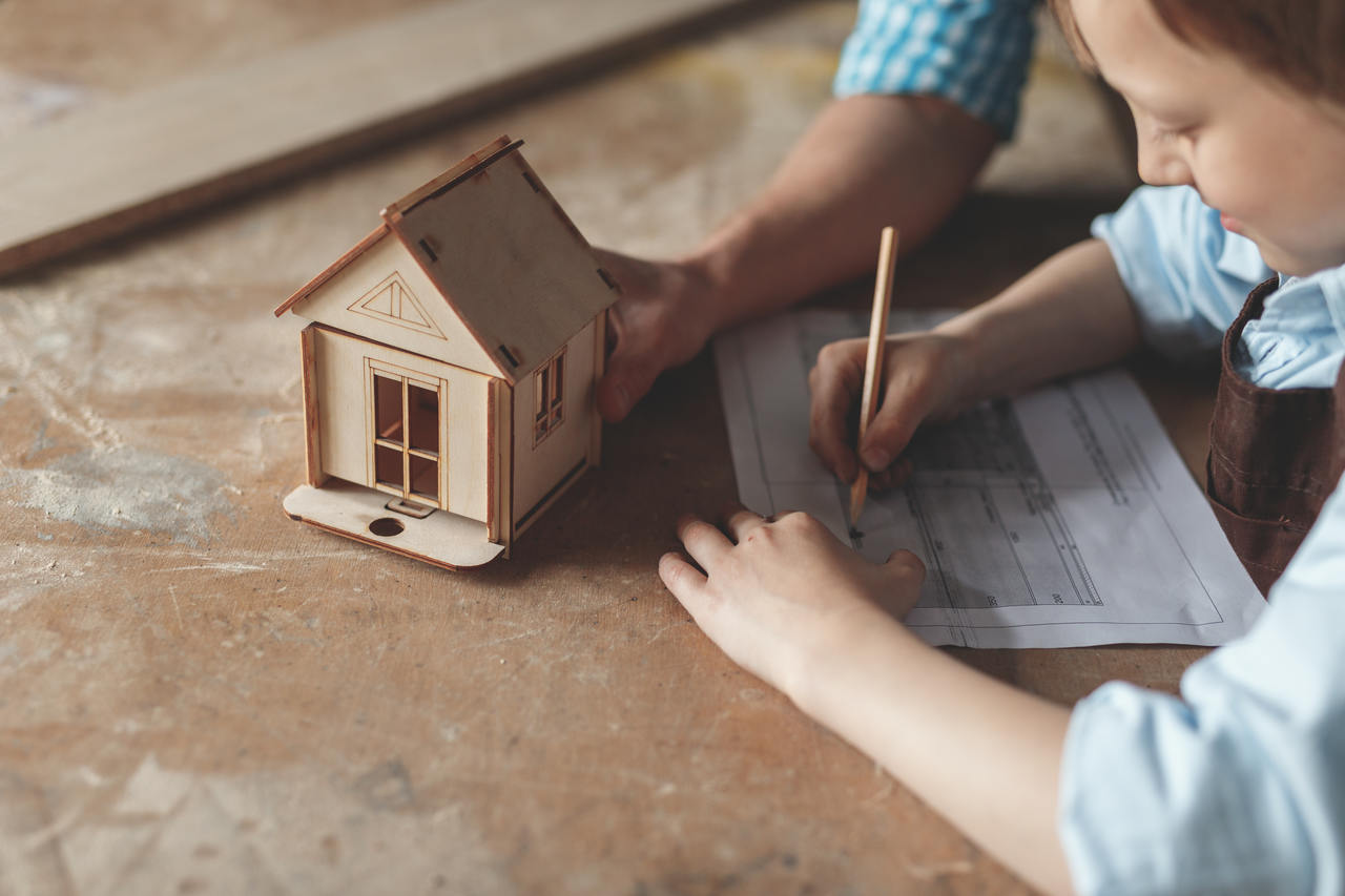 imar planı nedir, ahşaptan maket ev görseli ve çizim yapan bir çocuk