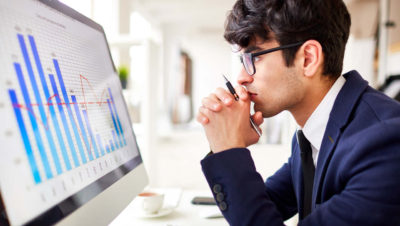 Deprem dayanıklılık testi-Bigisayar ekranında çizelge formunda analiz ve ekrana bakan takım elbiseli ve gözlüklü genç bir adam