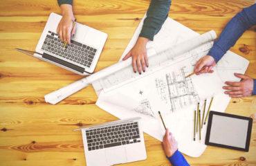 Ahşap bir masa üzerinde laptoplar, proje kağıtları, gereçler ve bunlarla çalışarak projeyi hazırlayan insanlar görseli