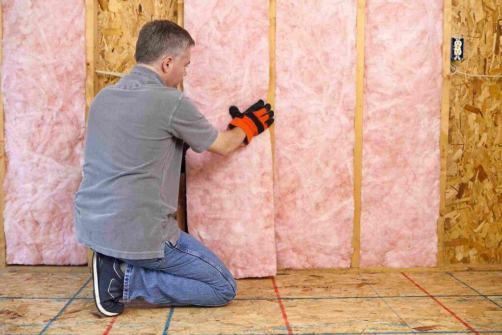 pembe renkli bir yalıtım malzemesini duvara yerleştiren işçi