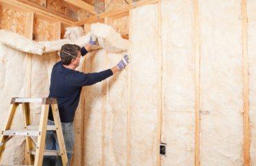 merdivende duran ve oda duvarına beyaz yalıtım malzemesiyle kaplayan işçi