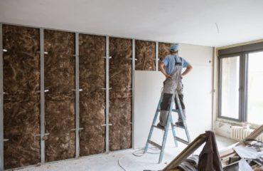 merdivende duran oda duvarına yalıtım malzemesi yerleştiren inşaat işçisi