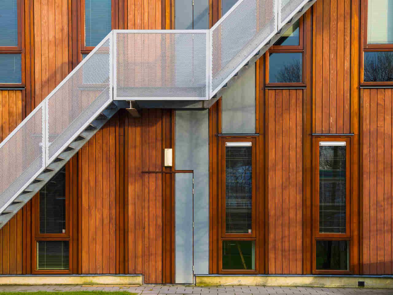 sürdürülebilir mimari örneği ahşap bina duvarı ve beyaz metal merdivenler