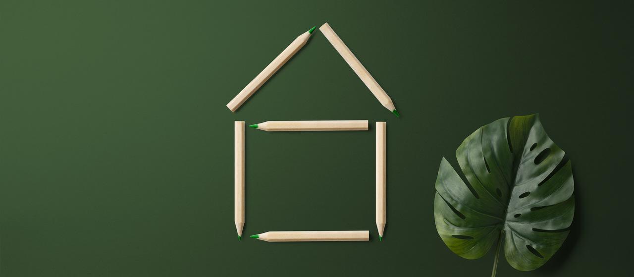 yeşil arkaplanda tahta çubuklarla yapılmış ev sembolü ve bir bitki yaprağı