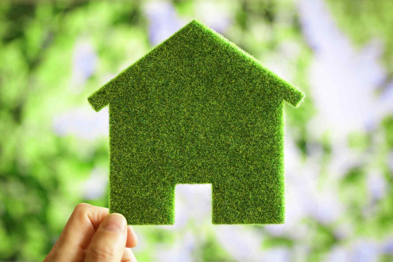 yeşil kartondan kesilmiş ev figürü tutan bir el